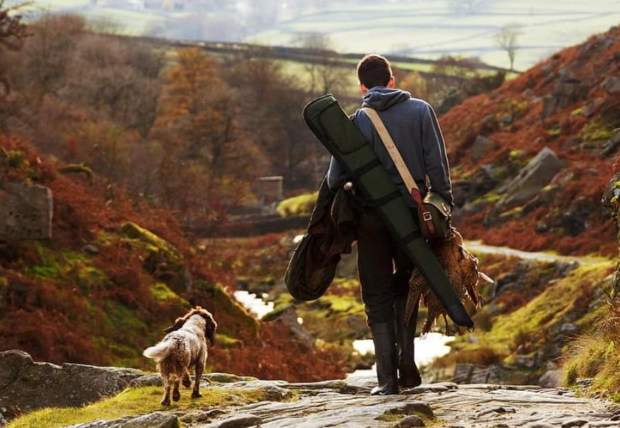 A hunter with his dog and a pheasant